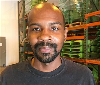 Bald man with facial hair wearing a black shirt.