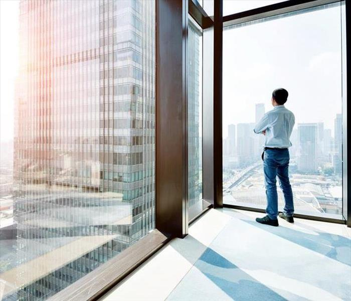 A man standing in an office looking out a window into the city.